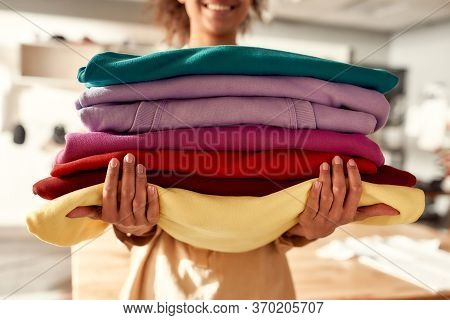 Cropped Shot Of Woman Holding Stack Of Colorful Sweatshirts, Hoodies While Standing In The Store. Cl