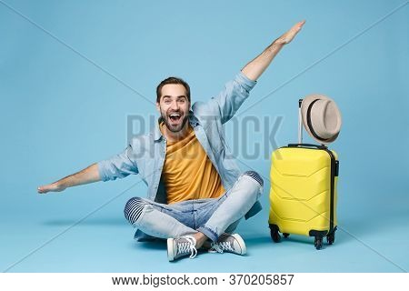 Excited Traveler Tourist Man In Yellow Clothes Isolated On Blue Wall Background. Male Passenger Trav