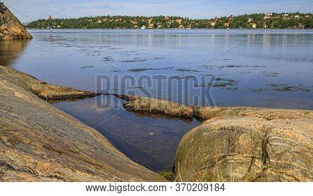 View Across Lilla Vartan Strait Onto The Shoreline Of Stockholm Suburbs, Lidingo Island With Traditi