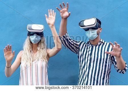 Young Couple Wearing Face Surgical Mask Having Fun With Virtual Reality Glasses During Outbreak - Mi