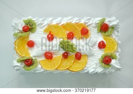 Piece Of Cake Decorated With Fruits And Cherry On Top. Many Fruit Cakes With Custard. Suitable As Ba