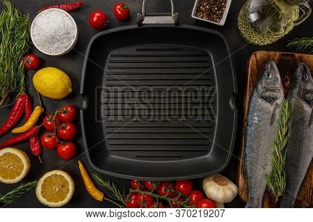 Grill Pan With Wo Fresh Seabass Fishes, Rosemary And Vegetable On A Black Background. Seafood Concep