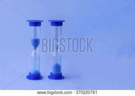 Two Hourglass With Falling Sand Inside Of Them As A Symbol Of Running Time, Lifetime And No Time. Sa