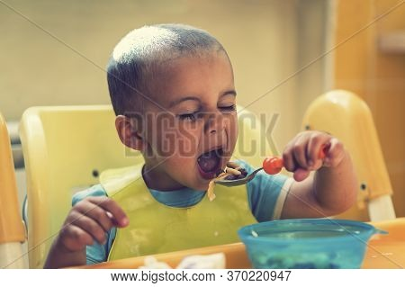 The Boy 2 Years Eats Porridge. Childrens Table. The Concept Of The Childs Independence. Cute Toddler