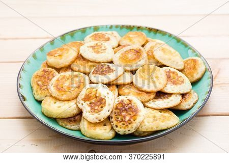 Trend Breakfast. Dutch Mini Pancakes On Plate On A Wooden Table. Close-up