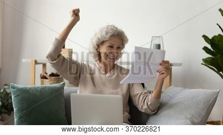 Happy Mature Woman Read Good News In Paper Correspondence