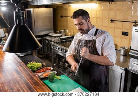 Serious handsome chef in apron sharpening knife with honing rod while preparing for cooking at restaurant kitchen