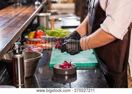 Close-up of unrecognizable chef in apron using knife while peeling red onion at commercial kitchen