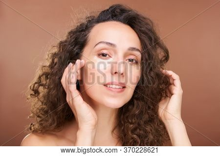 Pretty young woman looking at you putting revitalizing patches on undereye zone in front of camera over brown background