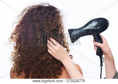Hands of young contemporary hairdresser holding hair dryer by healthy dark wavy hair of female client after washing it in salon
