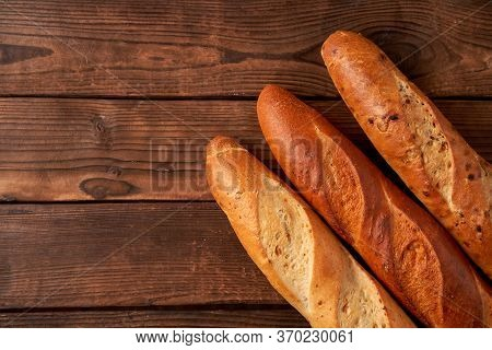 Three Crispy French Baguettes Lie On An Old Wooden Table With Free Space For Text Baguettes In Assor