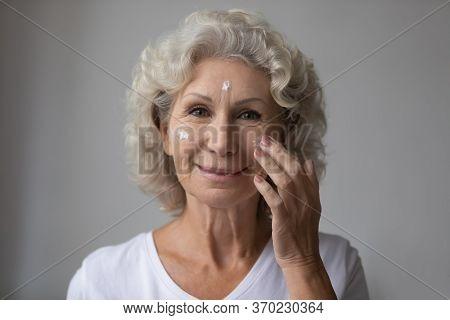 Portrait Of Elderly Woman Use Nourishing Facial Cream