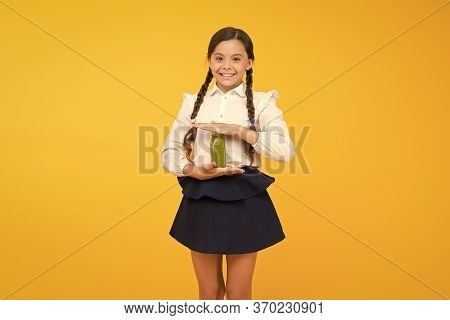 Thirst For Life. Thirsty Schoolgirl Holding Juice Bottle On Yellow Background. Quenching Thirst Duri