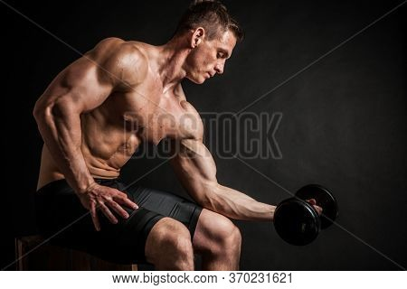 Fitness in gym, sport and healthy lifestyle concept. Handsome athletic man showing his trained body on dark background. Bodybuilder male model training biceps muscles with dumbbell.