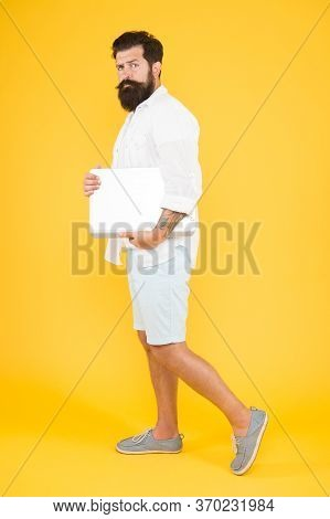 His Style Is A Lot More Casual. Bearded Man In Casual Hipster Style. Hipster Hold Laptop Yellow Back