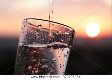 Pouring Clean Water Into Drinking Glass On Sunset Background. Concept Of Health And Freshness, Thirs