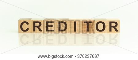 The Word Creditor Written On Wooden Cubes Isolated On A White Background.
