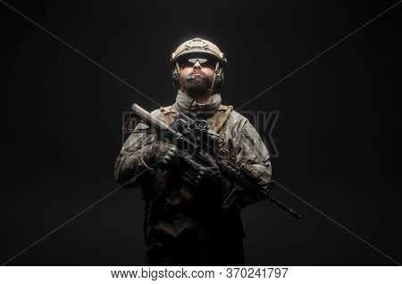 American Modern Special Forces Against A Dark Background, A Soldier In Military Equipment Holds Weap