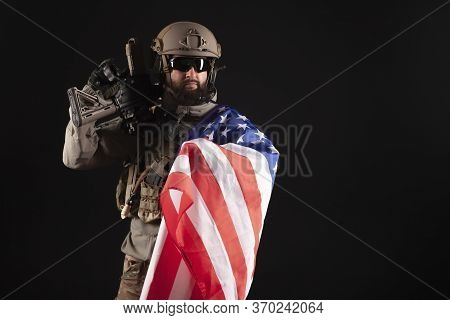American Special Forces Against A Dark Background, A Soldier In Military Equipment Holds Weapons And
