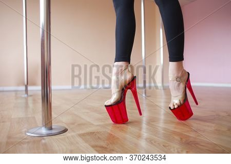 Pole Dance Concept, Girl With Stilettos Dancing A Striptease On A Pylon, Close-up Of Legs In High He