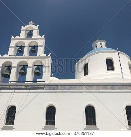 Domed Church With Bells In Santorini, Greece. Blue Dome, White Walls.