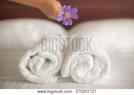 A Close Up Of A Maid Placing A Flower On A Set Of Towels On The Hotel Bed
