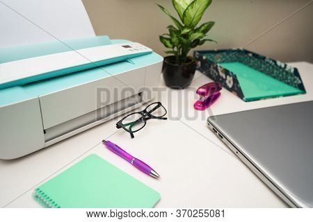 White Office Desk With Laptop, Printer, Glasses And Supplies. Selective Focus. Workplace Concept