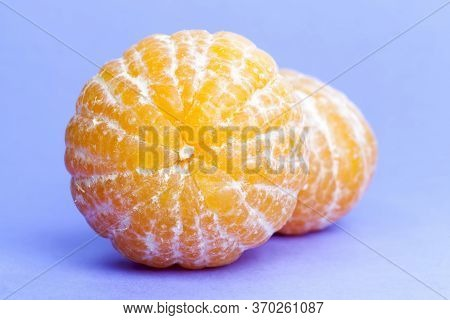 Peeled Delicious Orange Ready For Food, Chunks On A Purple Background, Close-up