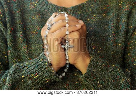 Close Up Of A Woman With Prayer Hands Folded To The Chest Holding A Rosary Beads. Building Deeper Re