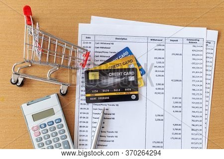 Credit Cards And Cart Supermarket And Calculator On Bank Statement On A Wooden Table