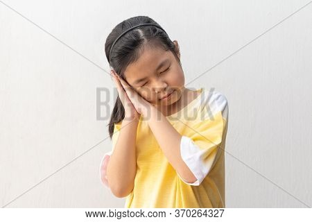 Asian Girl Standing And Sleeping Isolated On A Gray Background