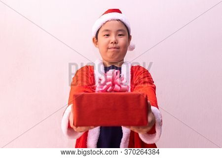 Asian Boy In Santa Claus Clothes Holding Gift. Merry Christmas