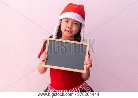 Asian Girl In Elf Clothes Holding Empty Board. Merry Christmas
