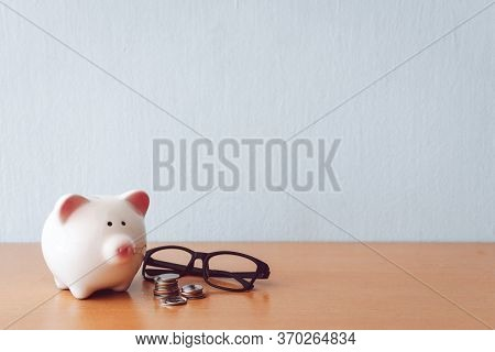 Piggy Bank, Calculator And Coins On Wooden Table