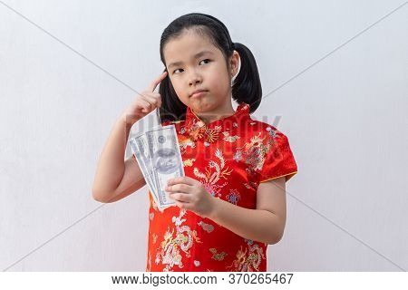 Asian Girl Wear Cheongsam And Take Red Envelopes And Thinking In Chinese New Year