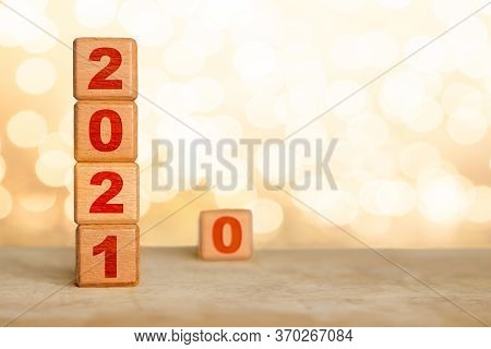 Happy New Year 2021 With Wood Cube Blocks And Leaving The Year 2020 Represented By 0 Behind To Be Fo