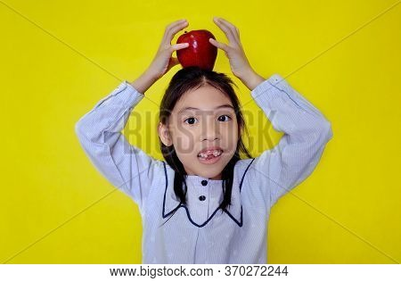 A Cute Young Asian Girl Trying To Balance A Red Apple On The Top Of Her Head, Cradling It With Her H