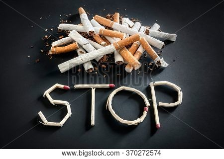 Stop smoking word written with broken matches and cigarette concept for quitting smoking