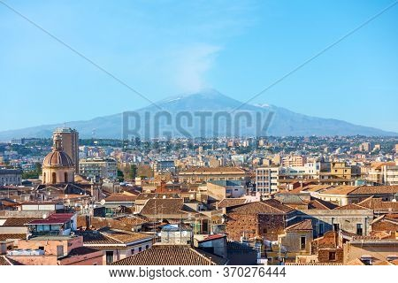 Roofs of the old town of Catania and smocking Etna volcano, Sicily, Italy