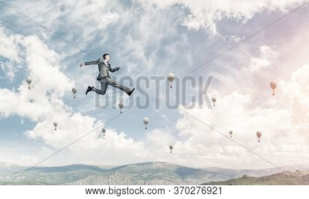Businessman In Suit Running In The Air As Symbol Of Active Life Position. Skyscape With Flying Ballo