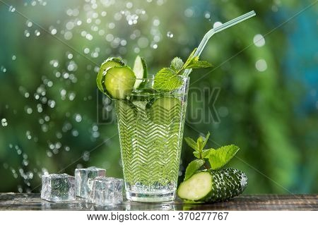 Refreshing Carbonated Drink With Ice And A Straw, In A Glass, Next To Cucumber And Mint