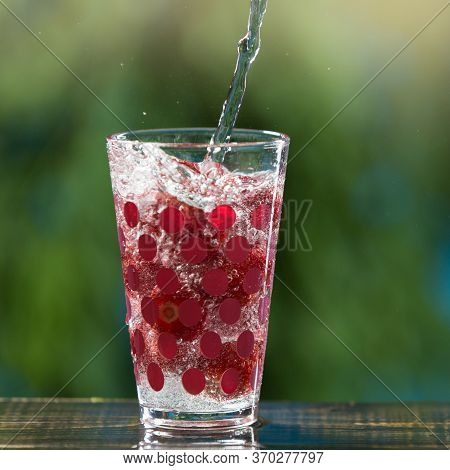 Soda Water Pouring Into A Glass Cup With Strawberries Illuminating The Drink Against