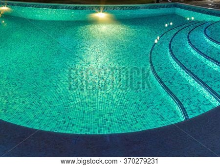 Pool At Night With Pure Blue Water Background. Top View Of Swimming Pool And Floor Texture Panorama