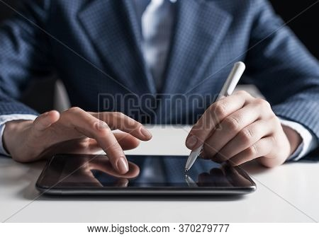 Man In Business Suit Using Digital Tablet Computer. Close-up Of Male Hand Holding Pen And Tablet Dev
