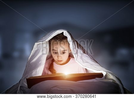 Little Girl Reading Magic Stories In Bed Before Going To Sleep. Pretty Child Hiding Under Blanket. C