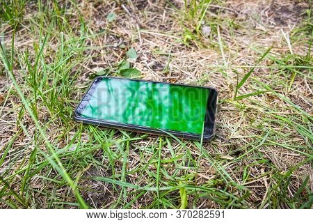 A Black Smartphone With A Green Touch Screen Is Lying In The Grass. Losing A Personal Item, The Conc
