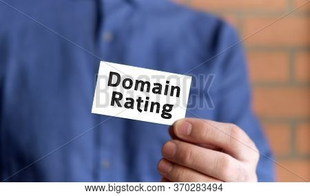A Man In A Blue Shirt Holds A Sign With The Text Of Domain Rating In One Hand