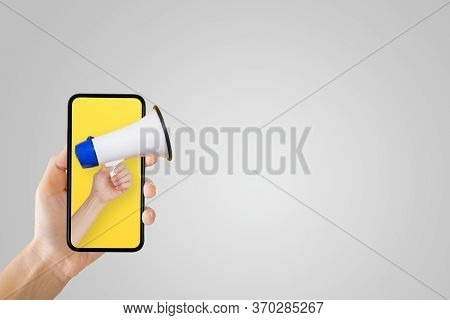 Business Communication And Marketing Concept : Hand Holding Megaphone In Smartphone For Announcement
