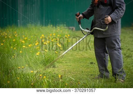 A Worker In Gray Protective Clothing With A Gas Lawn Mower In His Hands, Mows The Grass Next To The