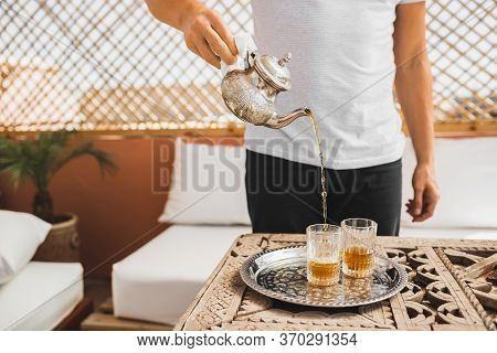 Man Holding In Hand Silver Vintage Teapot And Pouring Traditional Mint Sweet Moroccan Tea. Arabian H